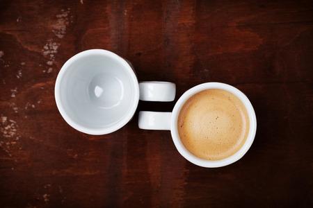 taza de café: Taza vacía y llena de café fresco en rústicos de madera de mesa, beneficios y daños de concepto de café, vista superior