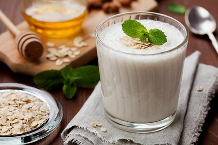 バナナのスムージーやオート麦と素朴な表面に飾られた蜂蜜ミントの葉を入れたミルクセーキの健康的な朝食 写真素材