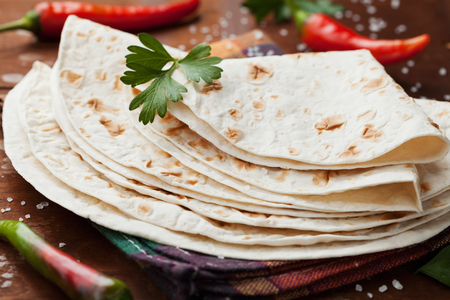 chili: Mexican flatbread tortilla on wooden table Stock Photo