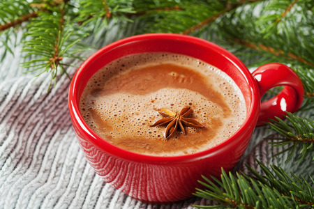 Cup of hot cocoa or hot chocolate on knitted background with fir tree, traditional beverage for winter time