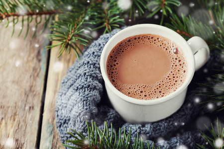 Cup of hot cocoa or hot chocolate on knitted background with fir tree and snow effect, traditional beverage for winter time