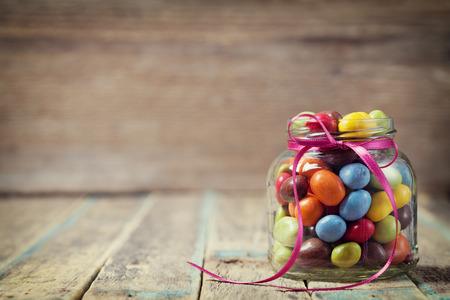 candies: Tarro de caramelos colorido decorado con un arco contra el fondo de madera, concepto de cumpleaños rústico