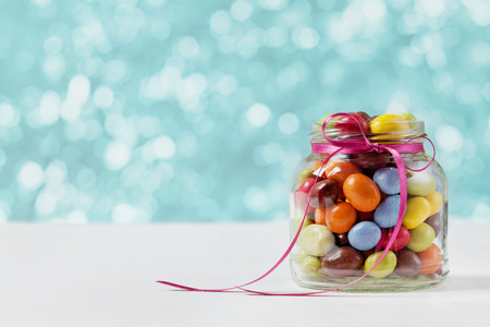 Colorful candy jar decorated with a bow against blue bokeh background, birthday concept Stock Photo