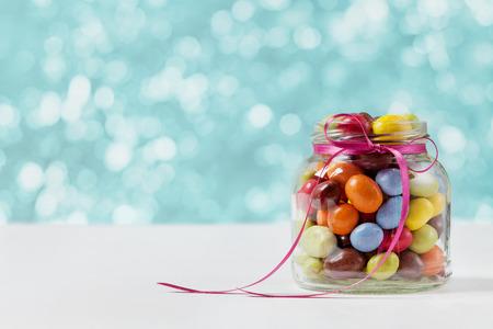dulces: tarro de caramelos de colores decorados con un lazo contra el fondo bokeh azul, el concepto de cumpleaños