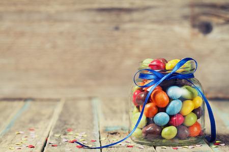 frasco: Tarro de caramelos colorido decorado con un arco contra el fondo de madera, concepto de cumpleaños rústico