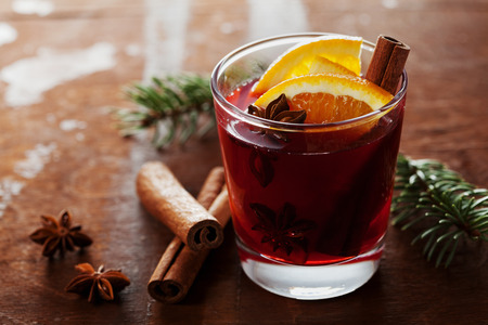 red evening: Christmas mulled wine or gluhwein with spices and orange slices on rustic table, traditional drink on winter holiday, magic light, selective focus