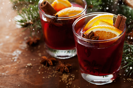 drinks: Christmas mulled wine or gluhwein with spices and orange slices on rustic table, traditional drink on winter holiday, magic light, selective focus