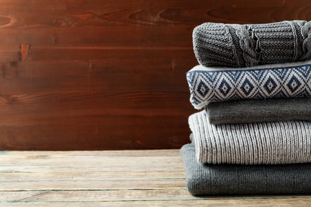 Pile of knitted winter clothes on wooden background, sweaters, knitwear, space for text Stock Photo - 48386765