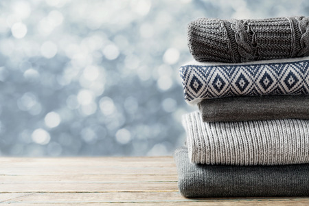 winter fashion: Pile of knitted winter clothes on wooden background, sweaters, knitwear, space for text