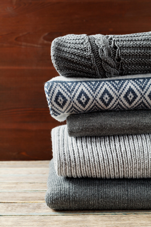 knitwear: Pile of knitted winter clothes on wooden background, sweaters, knitwear, space for text