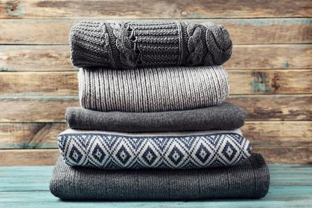 sueteres: Pila de ropa de punto de invierno sobre fondo de madera, suéteres, prendas de punto, espacio para el texto Foto de archivo