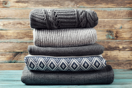 and in winter: Pile of knitted winter clothes on wooden background, sweaters, knitwear, space for text