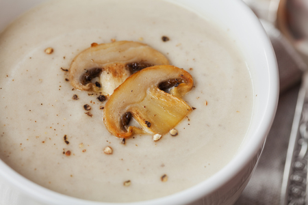 soup: Cream soup with mushrooms champignon and potato in white bowl, vintage style Stock Photo