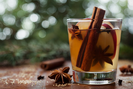 apple: Christmas mulled apple cider with spices cinnamon, cloves, anise and honey on rustic table, traditional drink on winter holiday, magical evening light, selective focus Stock Photo