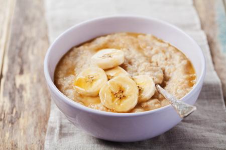 banane: Bol de gruau avec de la banane et sauce caramel sur la table rustique, chaud et petit déjeuner sain tous les jours, la nourriture de régime