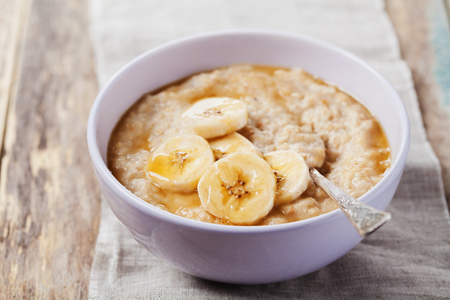 banana: Bowl of oatmeal porridge with banana and caramel sauce on rustic table, hot and healthy breakfast every day, diet food
