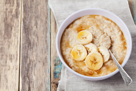 to the diet: Bowl of oatmeal porridge with banana and caramel sauce on rustic table, hot and healthy breakfast every day, diet food