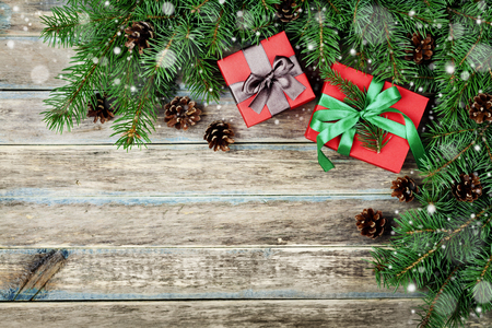 copy space: Christmas background with gift box, fir branch and conifer cone on wooden rustic board, festive snow effect, Christmas frame, top view with copy space