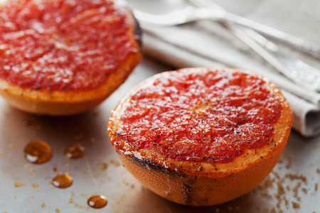 broiled: Vintage image of broiled grapefruit with brown sugar and cinnamon on metal surface, healthy dessert is good for breakfast or snacks Stock Photo