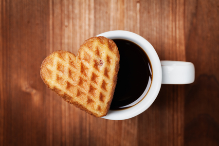 Waffle biscuits in shape of heart with cup of coffee on wooden background for Valentines day, top view