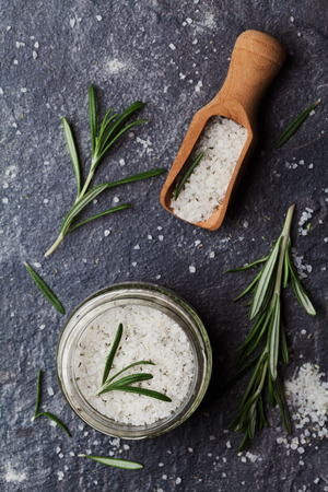 herb: Sea salt scented herb rosemary on black stone background, vintage style, top view Stock Photo