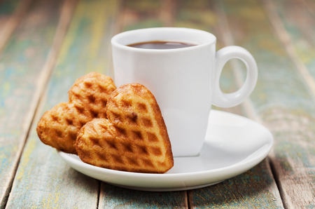 waffles: Waffle biscuits in shape of heart with cup of coffee on vintage background for Valentines day Foto de archivo