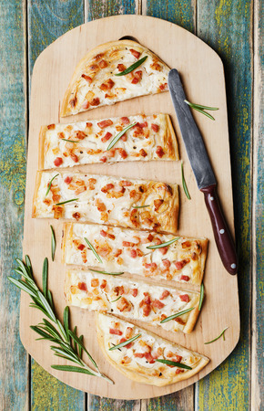 alsatian: Tart Flambe or Flammkuchen on wooden cutting board, traditional Alsatian pie, rustic style, top view Stock Photo