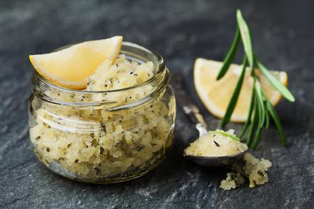 Body scrub zeezout met citroen, rozemarijn en olijfolie in glazen pot op stenen tafel, zelfgemaakte cosmetische voor Spa zorg Stockfoto