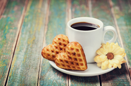 Waffle biscuits in shape of heart with cup of coffee and flower on rustic background for Valentines day, vintage toned Foto de archivo