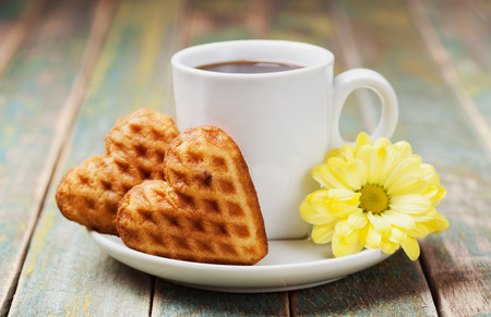 biscuits: Waffle biscuits in shape of heart with cup of coffee and flower on vintage background for Valentines day