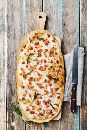flame: Tart Flambe or Flammkuchen on wooden cutting board, traditional Alsatian pie, rustic style, top view Stock Photo