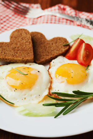 light breakfast: Fried eggs with fresh vegetables and toast in shape of heart on white plate, delicious Breakfast