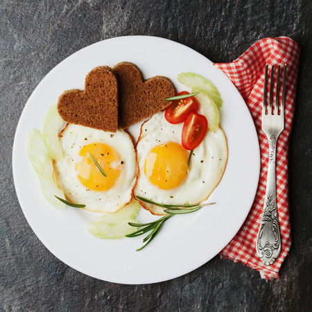 Fried eggs with fresh vegetables and toast in shape of heart on white plate, delicious Breakfast, top view