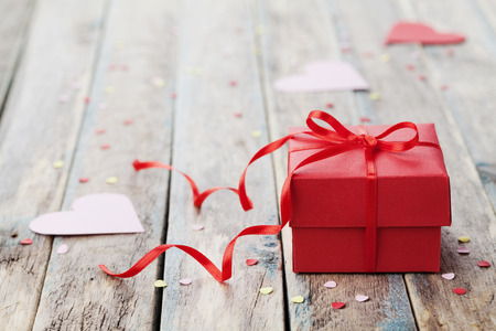 Gift box with red bow ribbon and paper heart on wooden table for Valentines day Foto de archivo