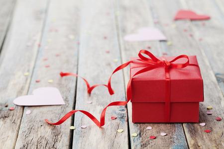 romance: Dárková krabička s červenou mašlí stuhou a papírové srdce na dřevěný stůl pro Oslavte den