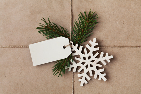 tied in: String or twine tied in a bow with tag, fir tree and wooden snowflake on kraft paper texture