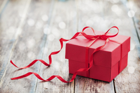 Gift box with red bow ribbon on wooden background for Valentines day, vintage toned Stock Photo