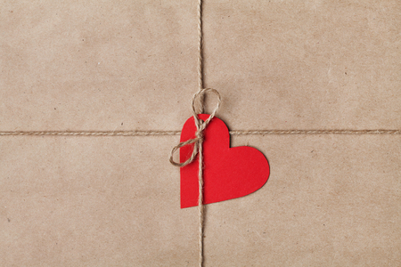 tied in: String or twine tied in a bow with tag in shape of heart on kraft paper texture