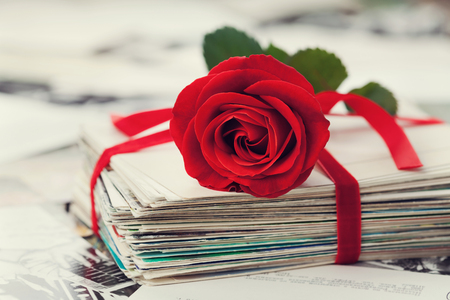 card design: Stack of postcard and photograph tied with velvet ribbon and red rose
