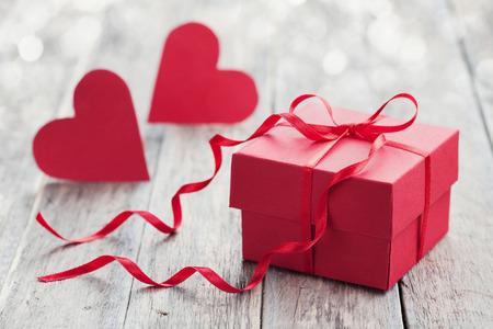 Geschenk-Box mit roter Schleife Band und zwei Papier Herz auf Holzuntergrund für den Valentinstag