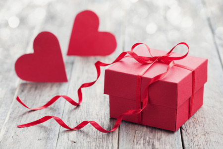 Pudełko z czerwoną kokardą wstęgi papieru i dwa serca na drewnianym tle na Walentynki