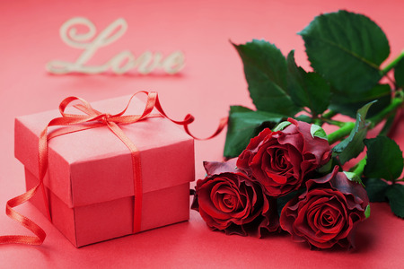 red gift box: Gift box with bow ribbon and red roses flowers holiday background for Valentines day