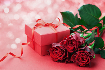 red rose bokeh: Gift box with bow ribbon and red roses flowers on holiday background for Valentines day