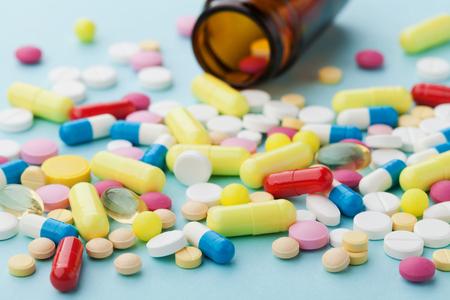 Pastillas de medicamentos de colores sobre fondo azul, el concepto farmacéutica