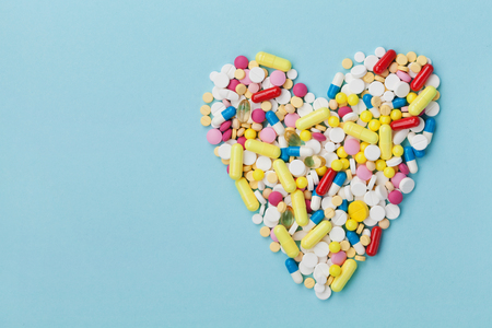 narcotism: Colorful drug pills in shape of heart on blue background, pharmaceutical concept