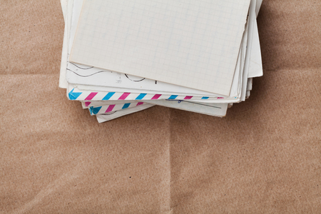 paper stack: Stack of old envelopes and letters on craft paper, top view Stock Photo