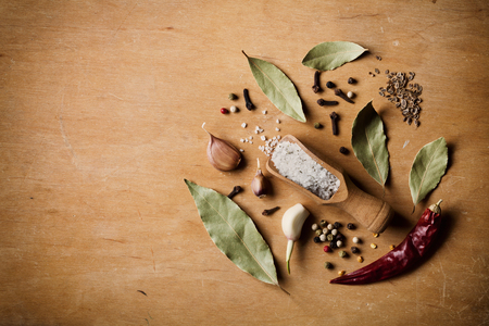 view on sea: Dry ingredients for cooking on wooden table. Sea salt, garlic, bay leaf, pepper and clove, top view. Rustic style