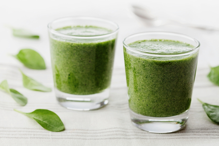 baby spinach: Green spinach smoothie in glass on white table, detox and diet food for breakfast