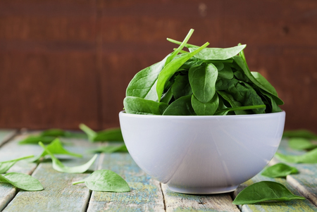 baby spinach: Fresh spinach leaves in bowl on rustic kitchen table, organic food Stock Photo