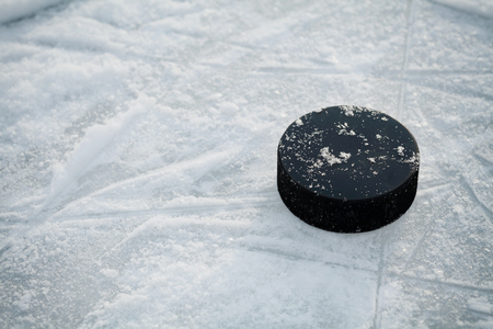 ice arena: Hockey puck on ice hockey rink Stock Photo